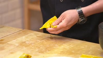 Close up of Jeremy Pang from School of Wok folding the wonton.