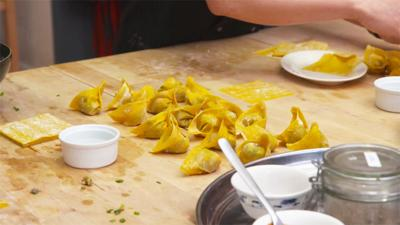 Rows of wontons are sitting on the kitchen worktop.