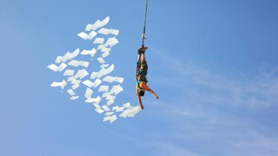 A bungee jumper with pages around him.
