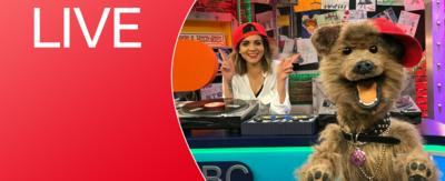 CBBC HQ Set with Lauren and Hacker in red hats and a live sign.
