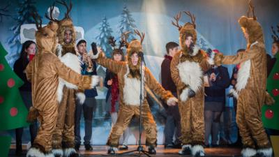 A group of school children on a hall stage dressed as reindeer perform a Christmas musical with Hank as Rudolf.