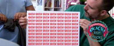 A doctor leans forwards, holding a sign that reads 'Green Green Green' in red.