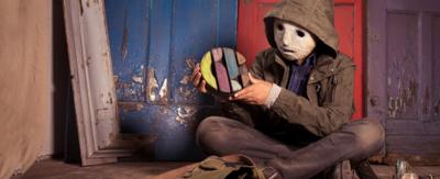 A boy with a white masked face with a hooded coat holds the CBBC logo in an old house, The Curious.