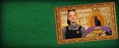 A girl in a school's uniform next to a framed picture of a black cat called Ember.
