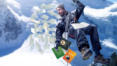 A man abseiling with books in snow.