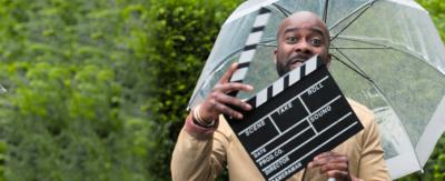 Melvin Odoom holding a clapper board.