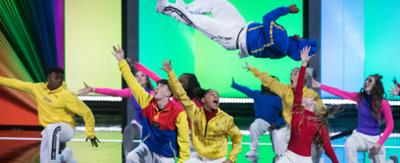 A group of young dancers on stage in colourful costumes, one dancer is leaping into the air.