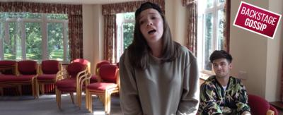 A girl in a grey hoodie and black cap is singing a song whilst Jaymi listens.