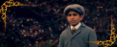 A Victorian boy looks on at something off camera in the distance. From CBBC series Hetty Feather.