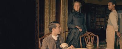 A serving boy and a older woman in black silk turn to listen to a seated young man, sat at the breakfast table, in a victorian morning room.