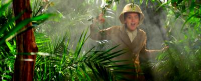 Jessica Ransom is dressed in old victorian style explorer clothes, peeking through forest foliage.