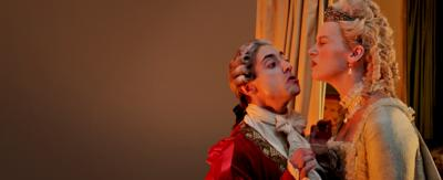 Ryan Sampson dressed as Louis XVI and Jessica Ransom dressed as Marie Antoinette make kissing faces at one another.