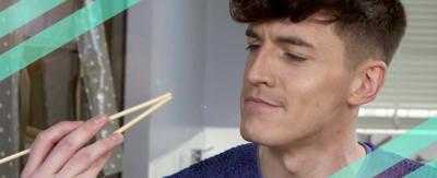 A man looking at chopsticks - 'How to use chopsticks'.