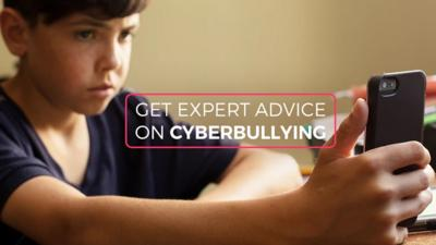 A boy holing his mobile phone, words overlayed read: 'Get Expert Advice on Cyberbullying'.