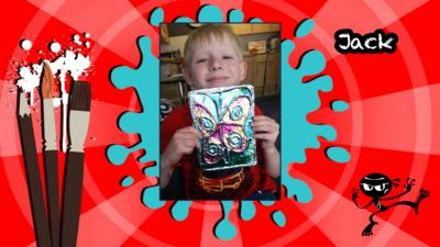 A photo of a boy holding a homemade butterfly art picture.