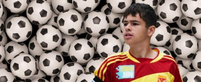 Jamie Johnson in front of multiple footballs.