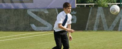 A boy playing football on a green football pitch.