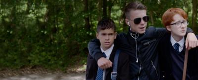 Three boys in school uniform in a wooded area looking ahead, the boy in the middle has his arms around the other two and is wearing sunglasses.