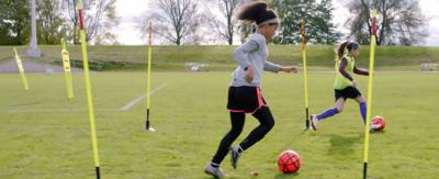 Two girls in a football field kicking footballs.