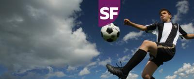A boy kicking a football in the air, Jamie Johnson.