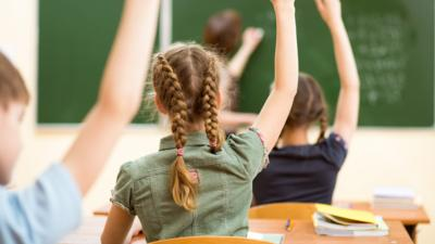 children in classroom holding arm up
