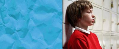 A boy leaning against school lockers looking worried