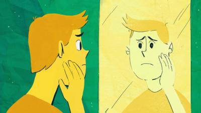 A boy looking in a mirror, worried