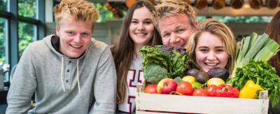 The Ramsay bunch sat in the kitchen and Tilly holding a box of vegetables.