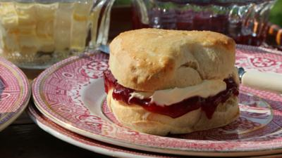 A heart shaped scone with jam and cream.