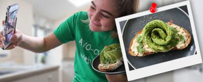 A girl (Matilda) taking a selfie with a plate of avocado toast.