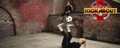 Girl midway through kicking ball in air. There is the MOTD kickabout logo.