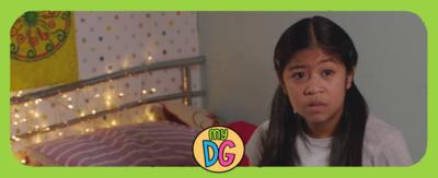 A girl, Taz, is sitting on a bed, looking worried. There is a logo that reads 'my DG'.