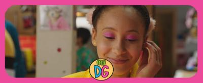 A young girl wearing a yellow jacket and pink eyeshadow (Candi-Rose from The Dumping Ground) smiling to herself.