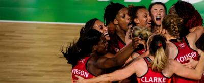 The England netball team hugging and celebrating.