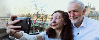 A girl taking a selfie with a man on a balcony in London, Nikki Lilly and Jeremy Corbyn.