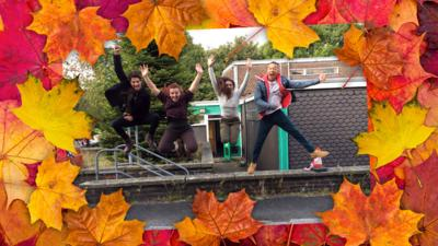 Photo of Wolfblood cast jumping into the air, surrounded bu autumnal leaves.