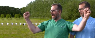 Two doctors in scrubs and goggles, stand in a field cheering.