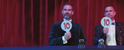 Two men sat behind a desk in sparkly suits holding up paddles with 10 on them.