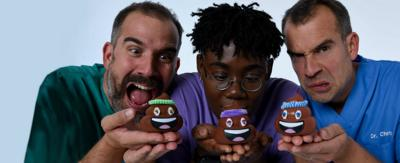 Three doctors in scrubs holding up small models of cartoon poo, Dr Xand, Dr Ronx and Dr Chris from Operation Ouch.