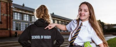A girl with a rugby ball pointing at another girl's back that says 'Rugby Team'