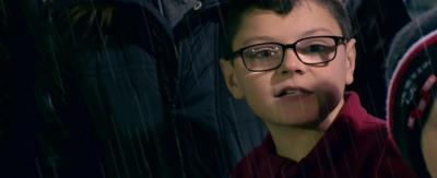 Young boy in the rain wearing glasses.