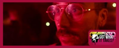 Portugal. The Man. A man with a moustache wearing glasses and looking into the distance.