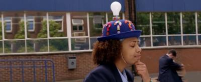 A girl in a school yard wearing a 'thinking cap' with a light bulb on the top.