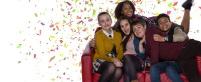 A group of boys and girls on a sofa with confetti in the background.