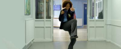 A girl in school uniform in a corridor giving the thumbs up, Jas from So Awkward.