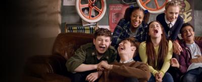 A group of girls and boys sat on a sofa all laughing, the cast of So Awkward.
