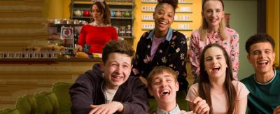 Six friends sat on a sofa in a cafe laughing, the cast of So Awkward.