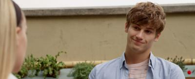 A boy standing outside in a blue shirt looking adoringly at a girl off-screen, Hunter.