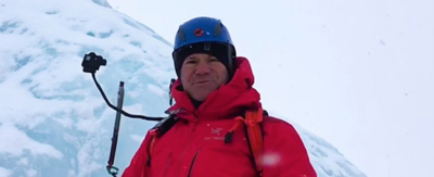 Steve Backshall in a red coat with a helmet on, faces a large ice wall.