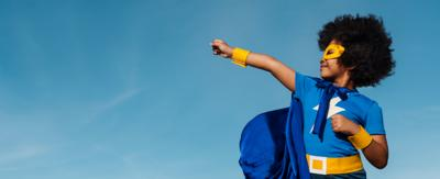 young girl with afro hair, wearing a blue and yellow superhero costume. She is fist bumping the air in a superhero pose.